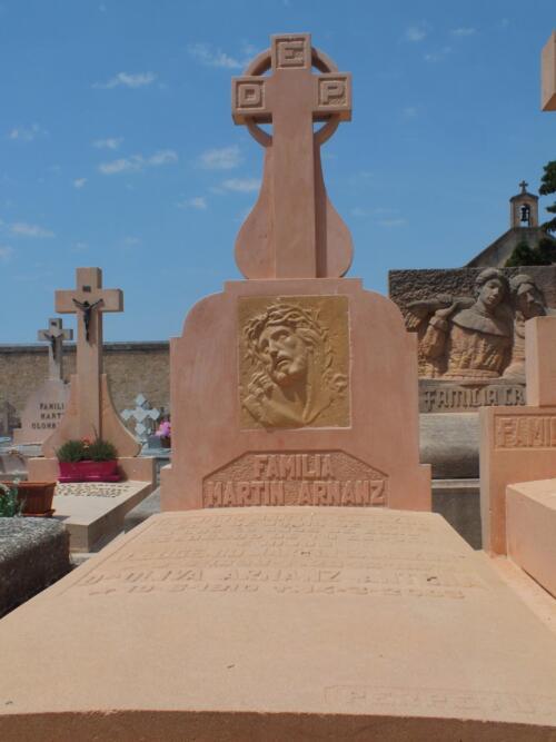 Panteón elaborado en piedra Rosa Sepúlveda con relieve de Cristo en el frente. Cementerio de Sepúlveda.