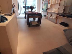 Solado, mostrador y estanterías de piedra Rosa Sepúlveda pulida en tienda de Madrid.