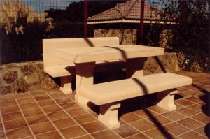 Mesa y bancos en chalet particular. Piedra Rosa Sepúlveda abujardada. Bancos con y sin respaldo. Medidas 180 cm de largo.
