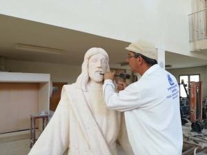 Trabajando a cincel los detalles de la cara del Corazón de Jesús de Fuentepiñel (Segovia). 2 m.