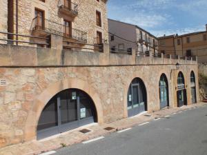 Arcos, muros de mampostería y barandilla de obra pública en Sepúlveda (Segovia). Piedra Rosa Sepúlveda abujardada.