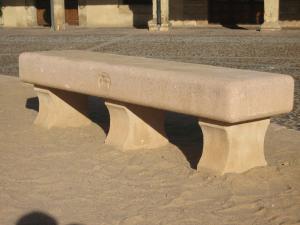Banco de piedra Rosa Sepúlveda con el escudo del Ayto. de Riaza tallado y colocado en la Plaza Mayor de Riaza (Segovia).