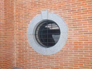 Ventana ojo de buey de granito en chalet de Soto del Real (Madrid).