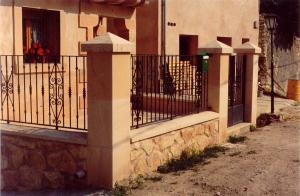 Pilares y albardillas de Piedra Rosa Sepúlveda abujardada y muros de mampostería en vivienda unifamiliar de Sepúlveda (Segovia).