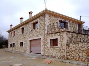 Fachada de Piedra Rosa Sepúlveda abujardada y mampostería en vivienda unifamiliar en Cerezo de Arriba (Segovia).