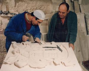 Juan Emilio y su padre, las dos últimas generaciones de la familia de canteros, esculpiendo un escudo por el método de talla directa.